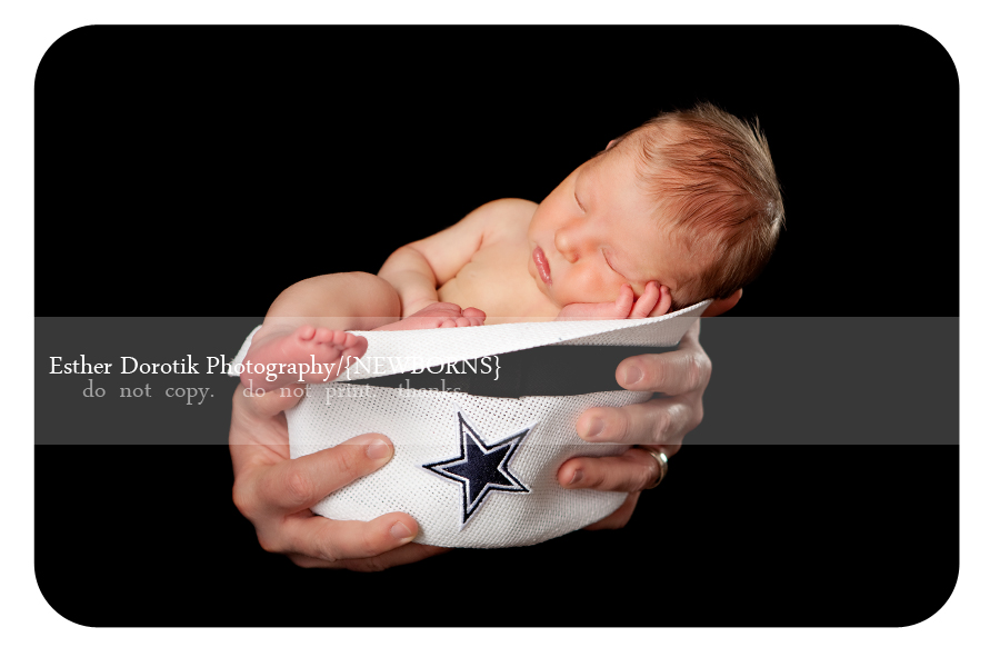 newborn-baby-girl-laying-in-Cowboys-Landry-hat-held-in-Daddy