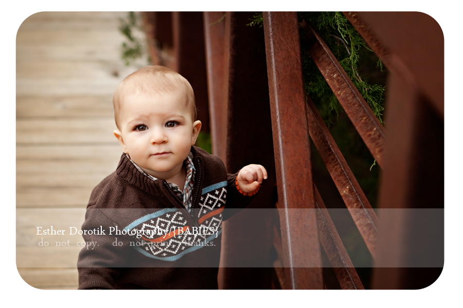 9-month-photography-of-baby-boy-sitting-on-bridge-in-trail-area