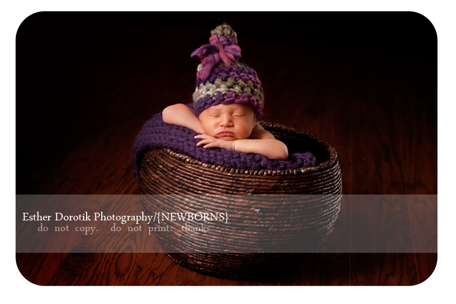 photograph-of-newborn-baby-girl-in-brown-basket-with-purple-knitted-hat