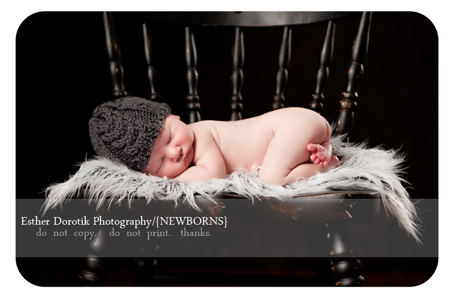 newborn-baby-boy-laying-on-big-black-chair-with-gray-rug-and-knit-hat