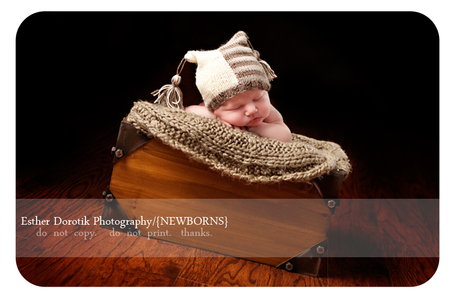 newborn-photograph-of-baby-boy-laying-in-basket-with-tassel-hat-on