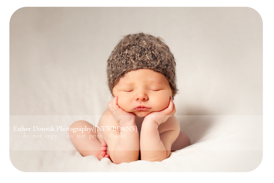 newborn-hands-under-the-chin-pose-with-brown-beanie