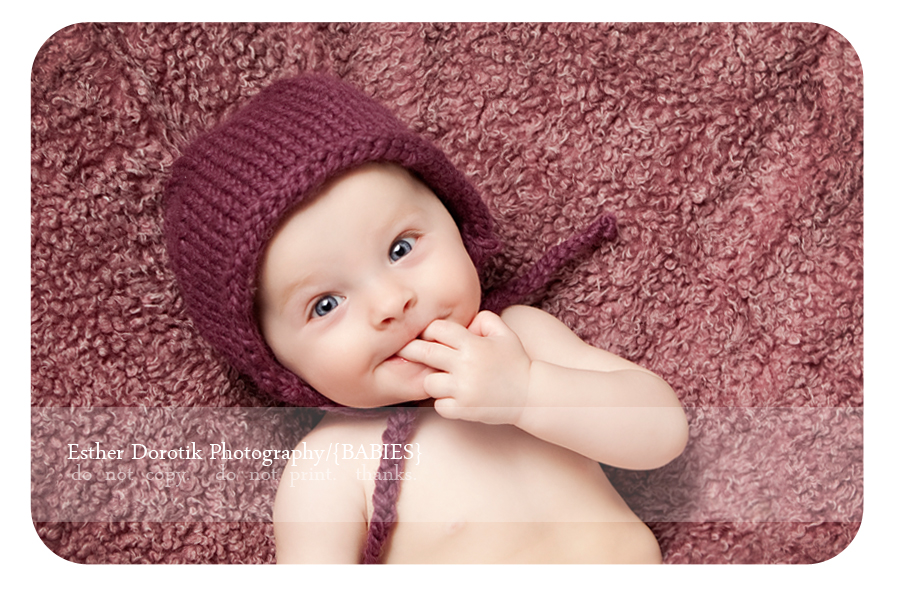 6-month-old-photograph-laying-on-fur-with-purple-hat