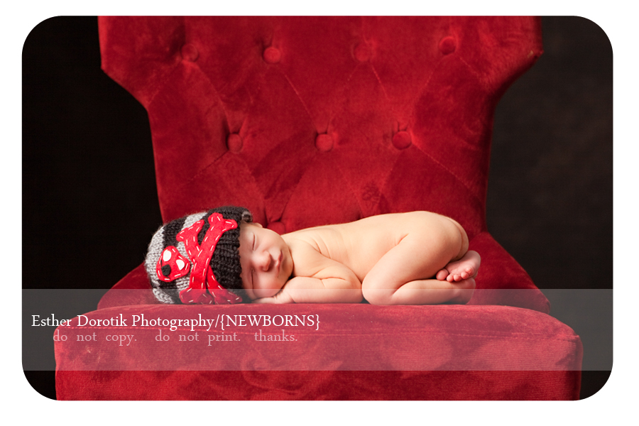 Dallas-newborn-baby-boy-laying-on-red-chair-with-cross-bones-hat