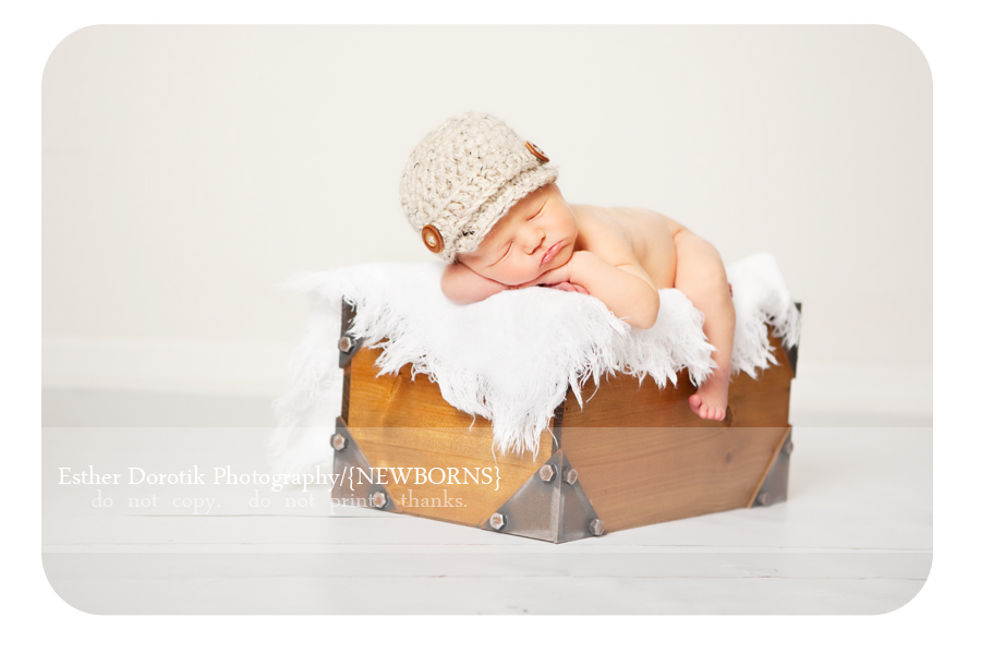 newborn-baby-boy-lying-on-blanket-with-newsboy-hat-and-leg-hanging-off-basket