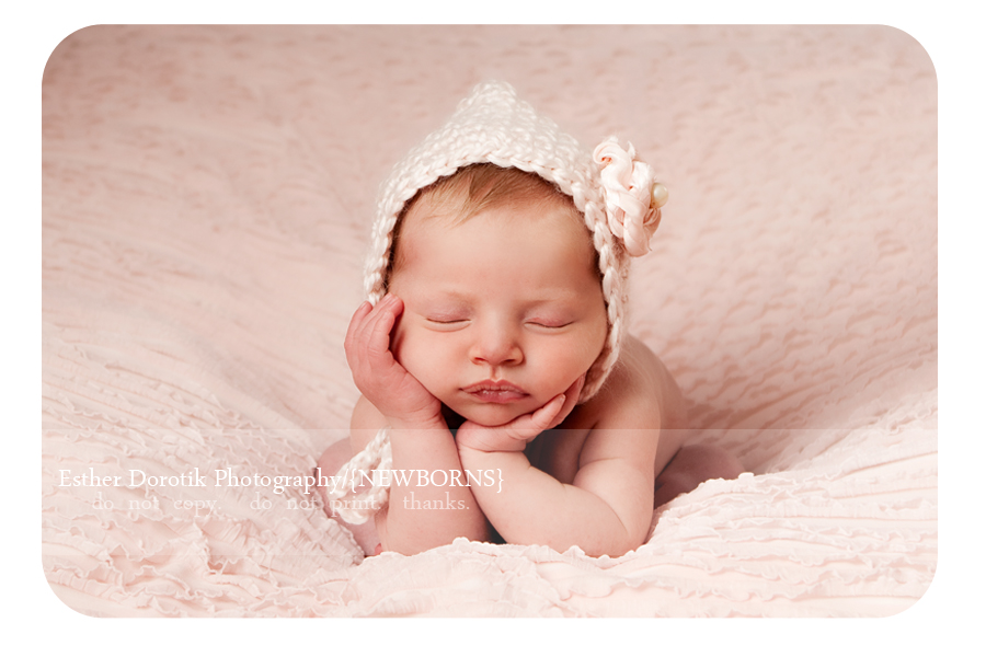 newborn-photography-of-baby-girl-with-hat-on-and-hands-under-chin