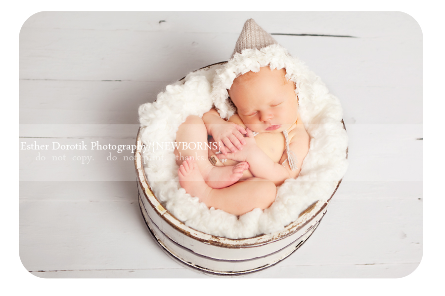 newborn-picture-of-baby-girl-in-basket-with-rosette-knit-hat