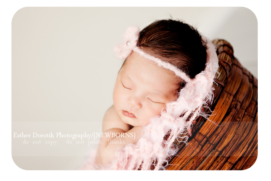 newborn-laying-in-bamboo-basket-with-soft-pink-headband-by-Dallas-photographer