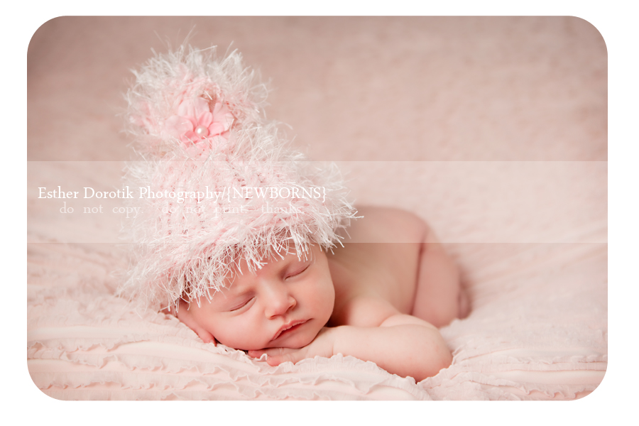 picture-of-newborn-girl-laying-on-blanket-with-hat-on