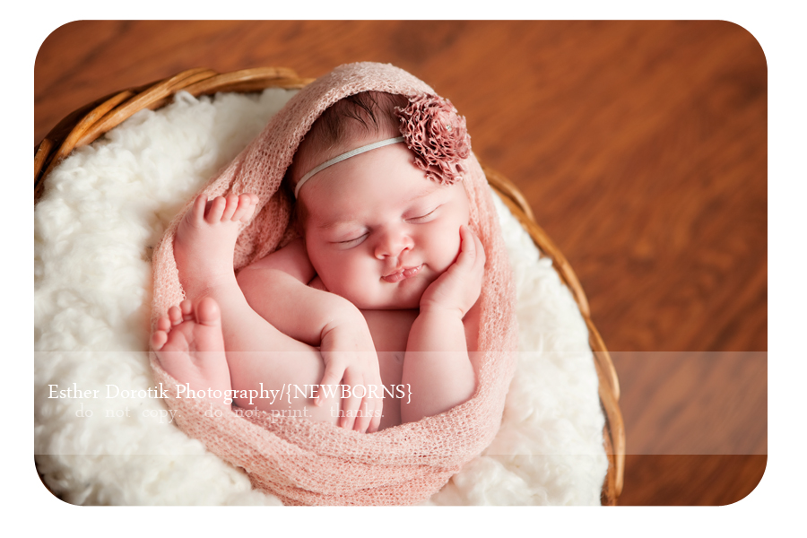 newborn-photography-of-baby-girl-in-knit-wrap-laying-in-basket