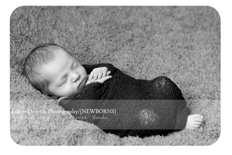 newborn-baby-wrapped-in-knit-with-hands-by-face-in-black-and-white