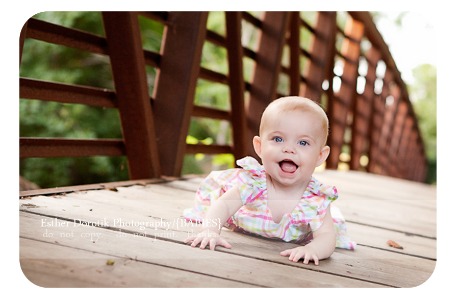 photograph-of-6-month-baby-girl-laying-on-bridge-with-big-smile