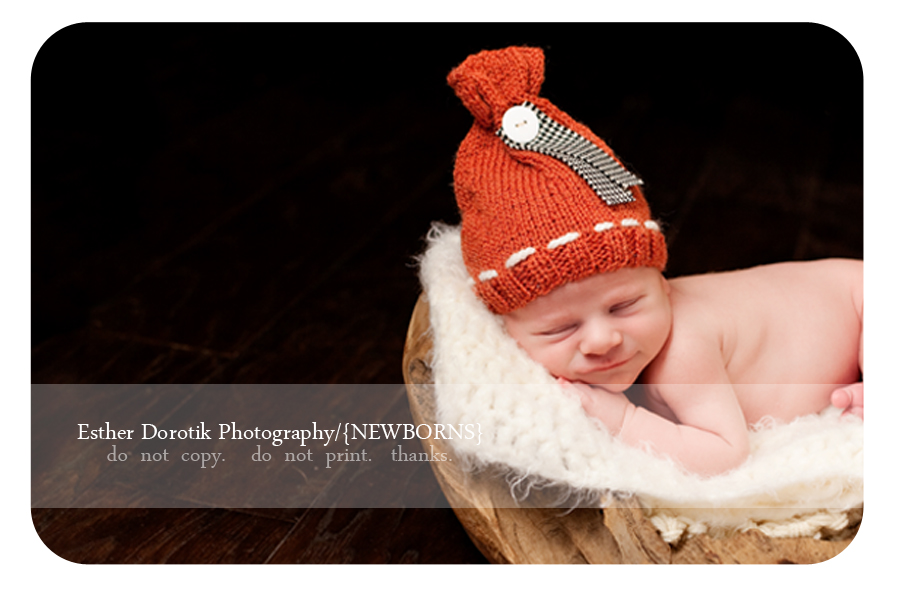 new-baby-laying-on-wood-tree-with-orange-hat-smiling-taken-by-Irving-photographer