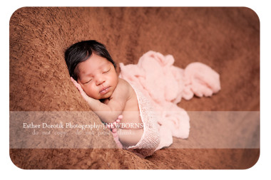 newborn-baby-girl-laying-on-blanket-with-wrap-around-her