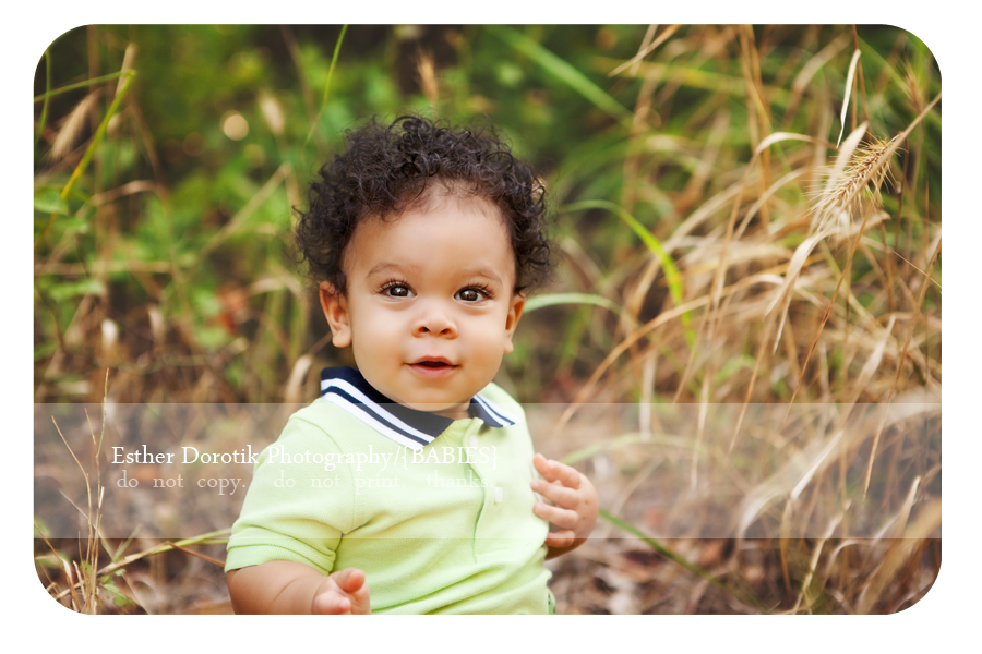 Plano-photographer-captures-9-month-boy-sitting-in-Flower-Mound-grass-with-green-shirt