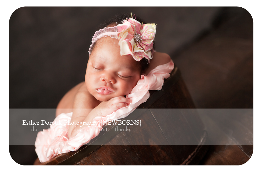 Richardson-baby-photographer-captures-newborn-infant-laying-in-bowl-with-pink-headband-smiling