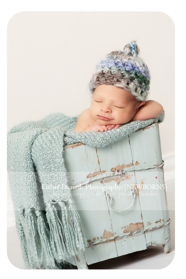 6-day-old-newborn-baby-in-blue-antique-bucket-with-hat-on-smiling-captured-in-Dallas-photography-studio