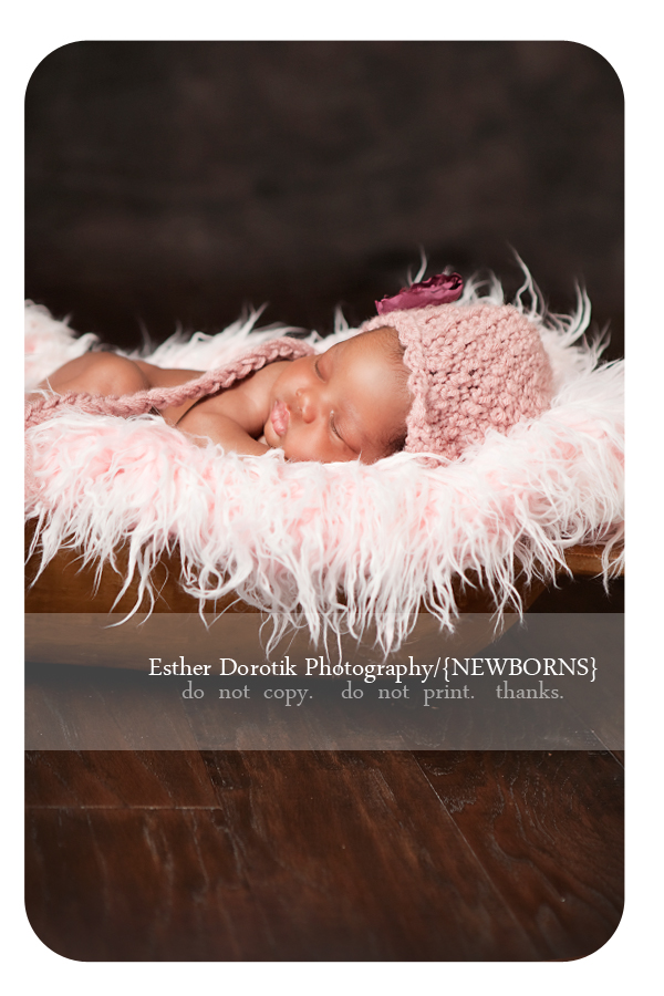 3-week-old-infant-girl-laying-in-fur-with-rose-ear-flap-hat-taken-by-Irving-newborn-baby-photographer-