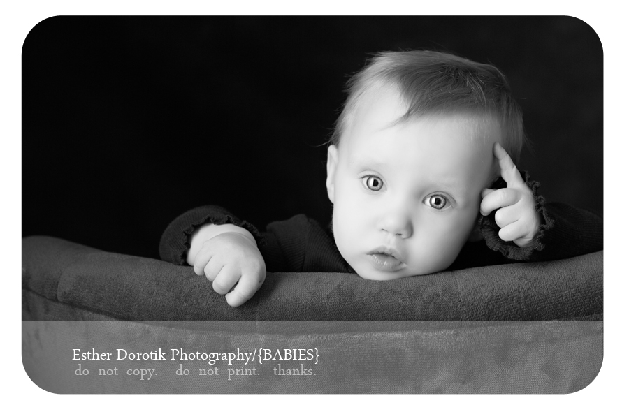 black-and-white-of-baby-girl-sitting-on-chair-with-finger-on-forehead-taken-by-unique-baby-photographer
