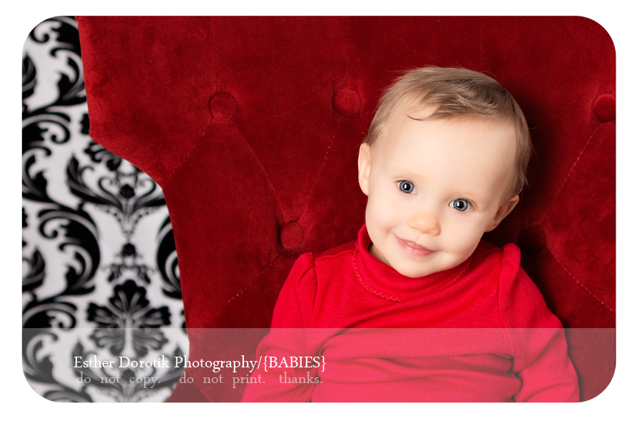 smiling-9-month-infant-girl-sitting-in-red-chair-taken-in-Highland-Village-photography-studio