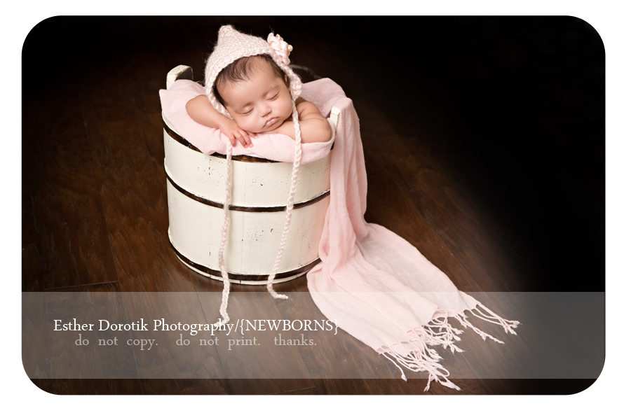 8-week-old-newborn-baby-sleeping-in-cream-basket-with-pink-newborn-hat-on-photographed-by-Dallas-baby-photographer