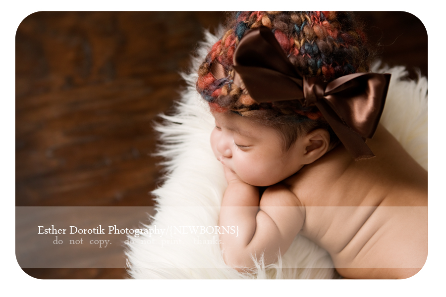 Dallas-family-photographer-captures-unique-position-of-newborn-baby-laying-in-fur-with-knit-hat-on