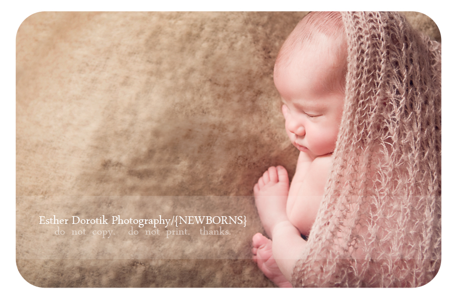 new-born-baby-posing-on-bean-bag-with-blanket-and-knit-wrap-around-her