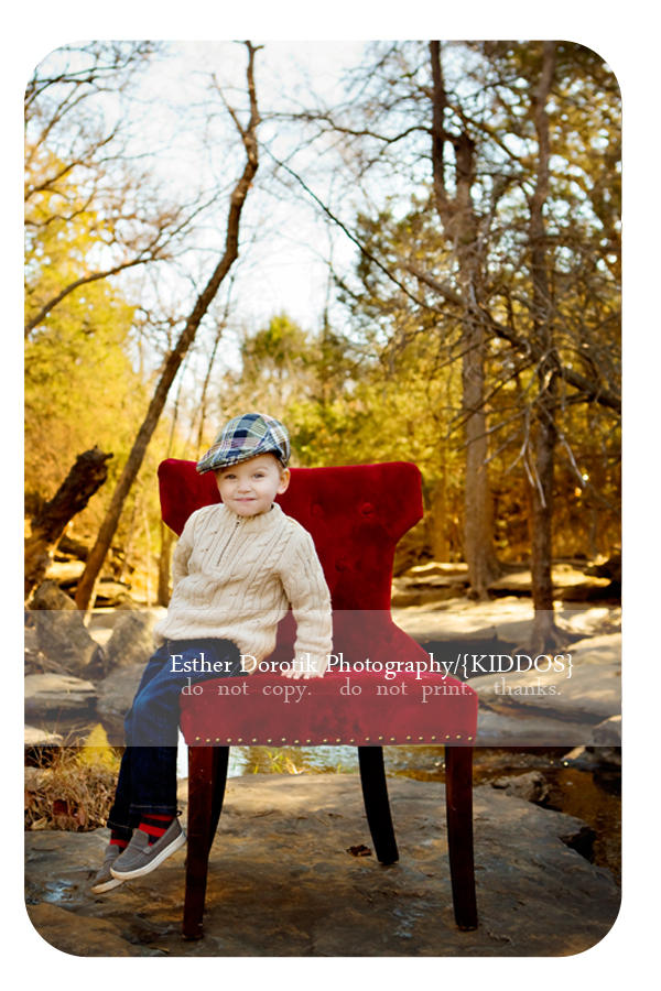 Dallas-children-photographer-captures-toddler-boy-sitting-in-red-chair-on-rock-in-creek-area