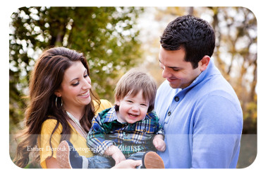 fun-outdoor-family-picture-of-15-month-old-laughing-in-the-arms-of-parents