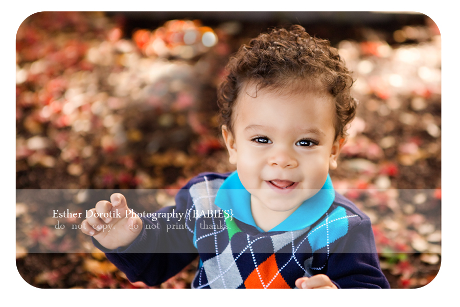 Dallas-family-photographer-captures-baby-boy-smiling-with-bright-colorful-sweater-on