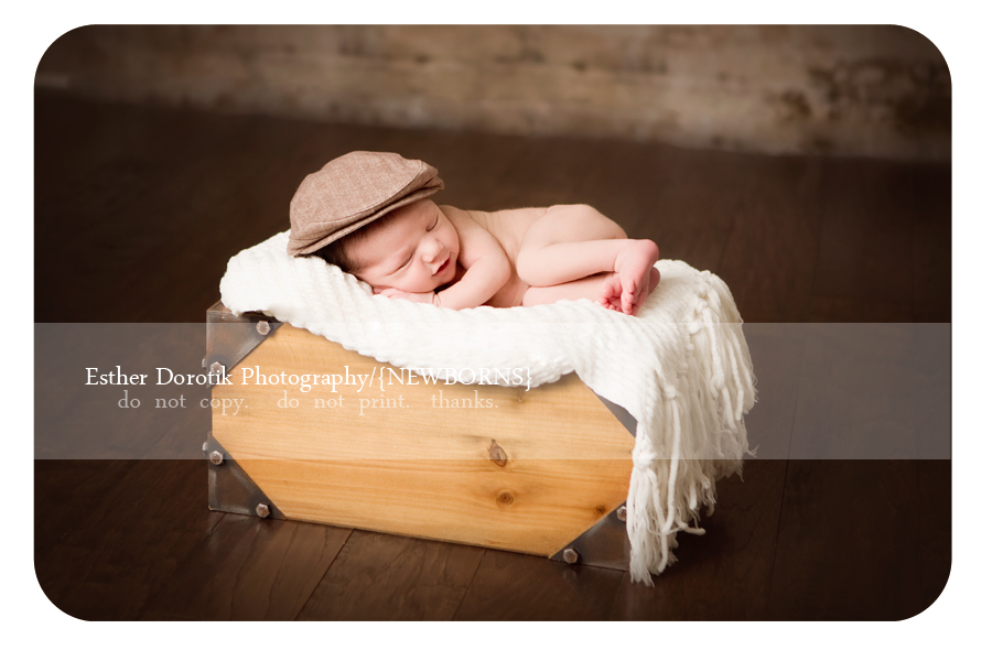 The-colony-newborn-photographer-captures-baby-laying-in-basket-with-hat-on-smiling