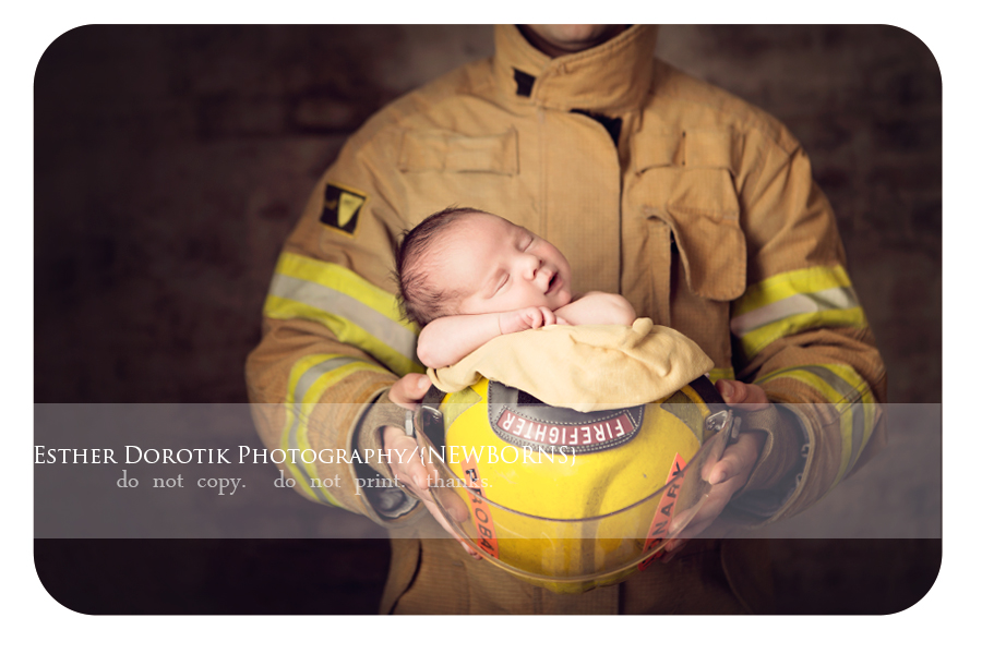 Newborn baby laying in firefighter hat in daddy