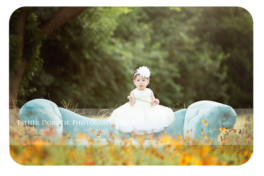 one-year-old-photography-of-baby-girl-sitting-on-blue-couch-in-yellow-wildflower-field