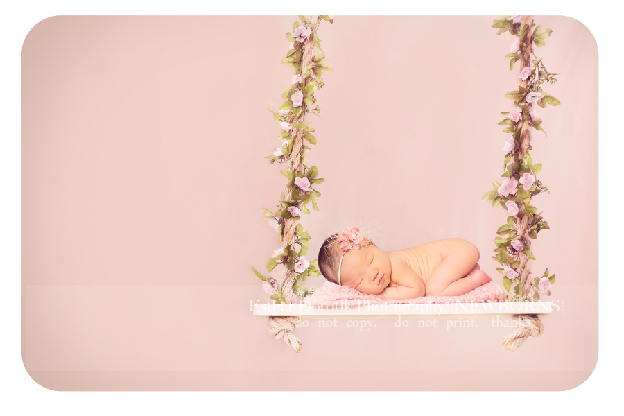 Newborn baby girl laying on swing with pink