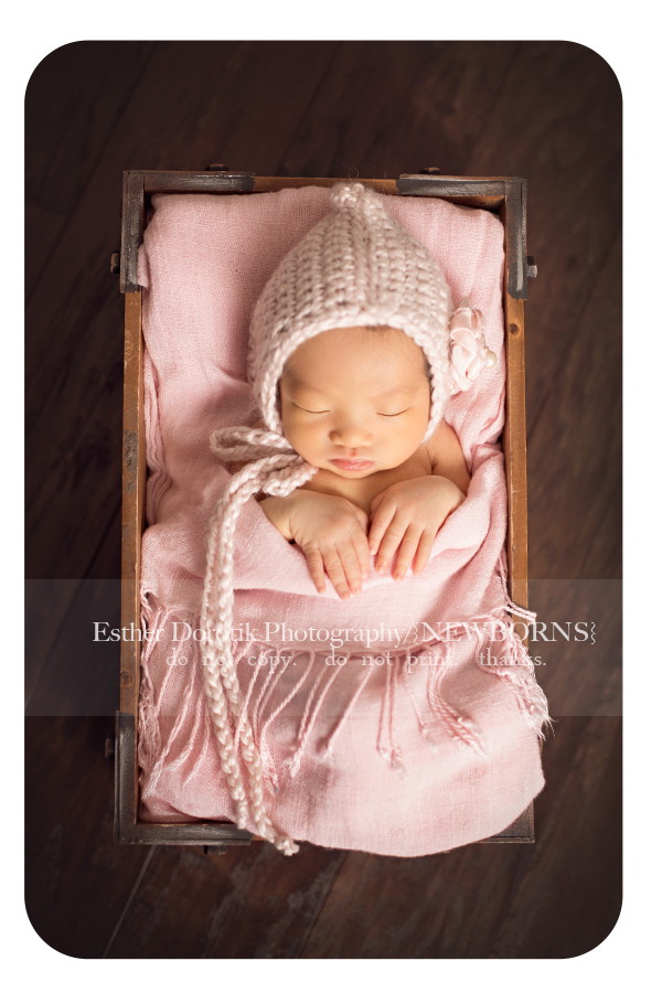 newborn-baby-girl-laying-in-blanket-with-pink-bonnet-by-Dallas-newborn-photographer