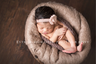 newborn-baby-pictures-of-girl-laying-in-basket-with-headband-and-smiling-byDallas-newborn-photographer