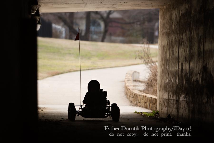 silloette-lifestyle-photo-of-kid-riding-gocart-through-tunnel