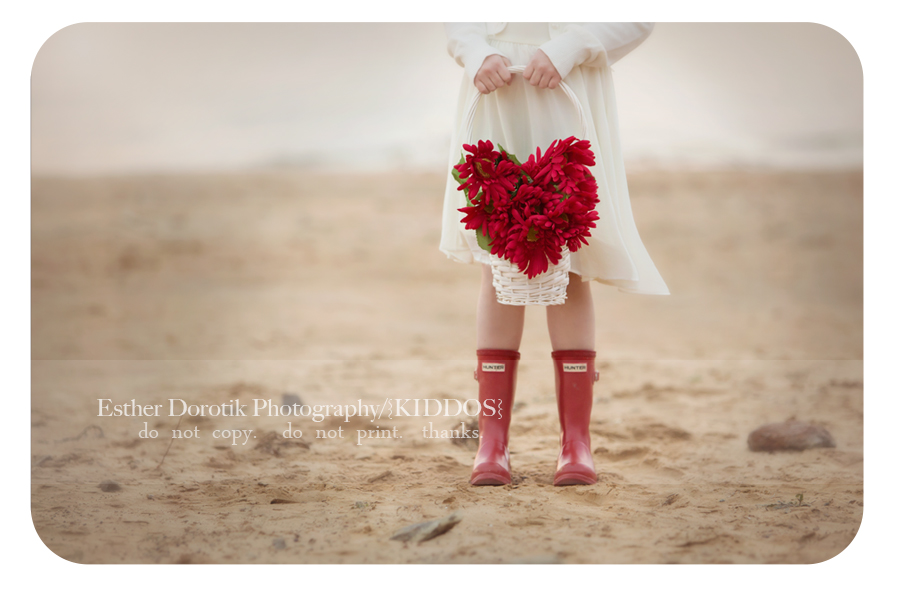 picture-of-little-girl-in-white-dress-and-red-Hunter-boots-holding-red-heart-shaped-flowers-by-Dallas-valentine