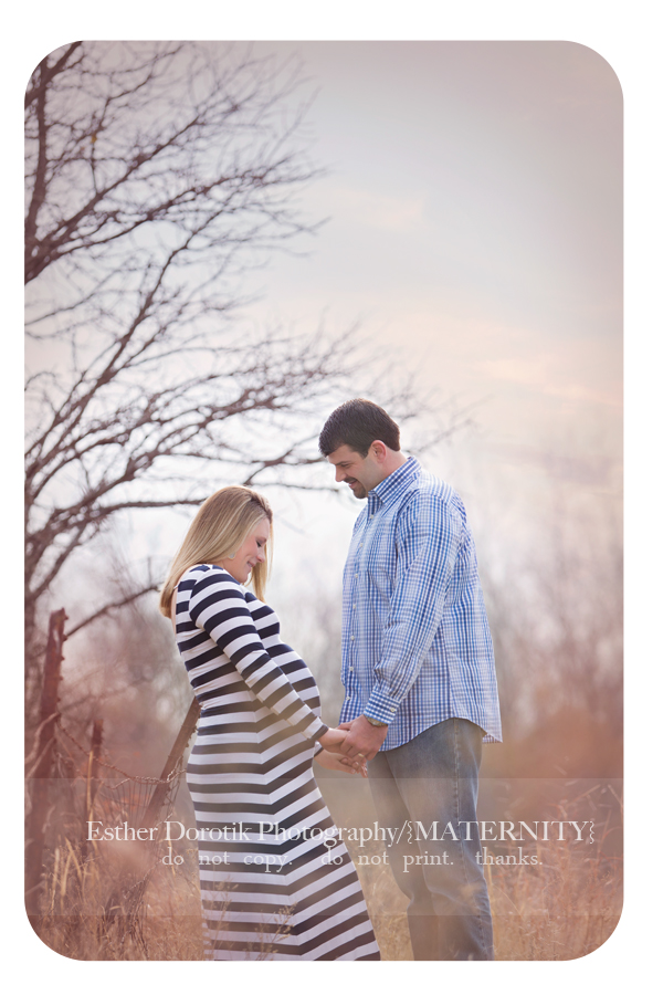 expecting-couple-standing-in-tall-grass-with-old-wire-fence-by-Dallas-newborn-and-maternity-photographer