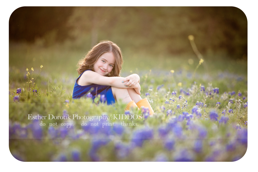picture-of-6-year-old-girl-sitting-in-blue-bonnet-field-with-blue-outfit-and-yellow-boots-by-Dallas-child-photographer