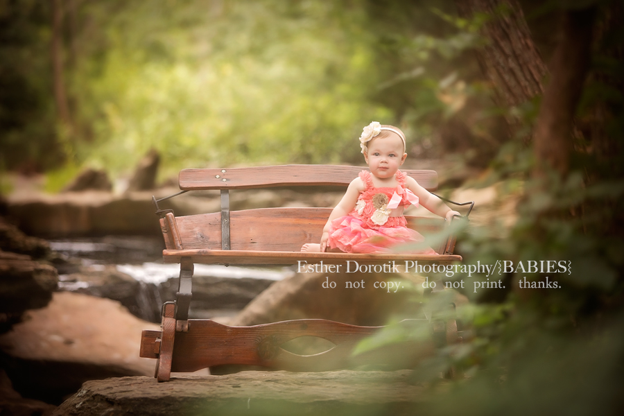 picture-of-one-year-old-girl-sitting-on-antique-saddle-bench-in-creek-by-Lewisville-baby-photographer