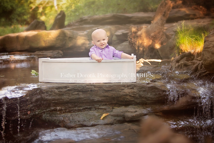 picture-of-one-year-old-boy-sitting-in-boat-in-creek-by-Dallas-infant-photographer