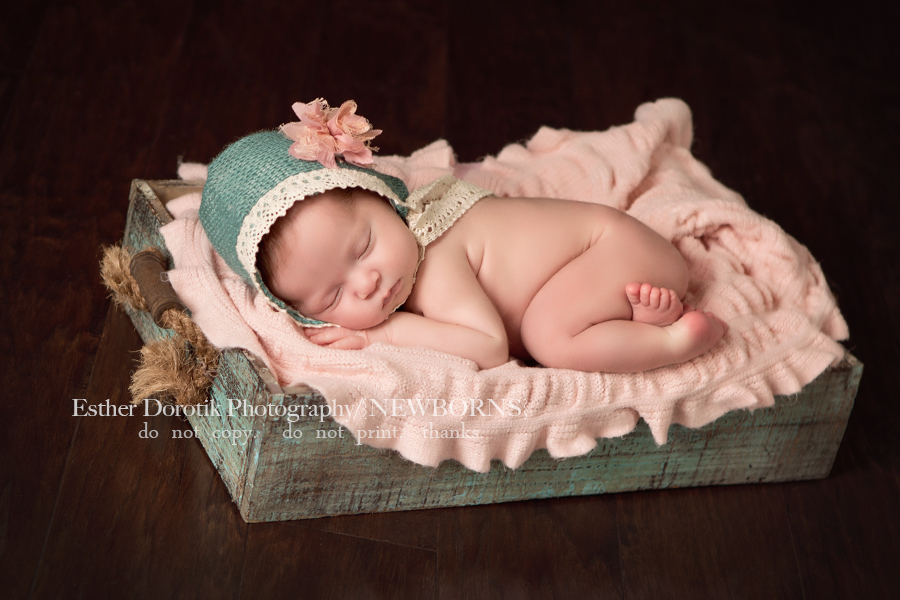 picture-of-newborn-with-teal-hat-on-laying-in-antique-basket-by-Fort-Worth-newborn-photographer