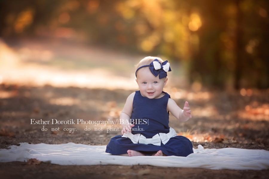 picture-of-6-month-baby-girl-in-field-with-blue-dress-on-by-Dallas-baby-photographer